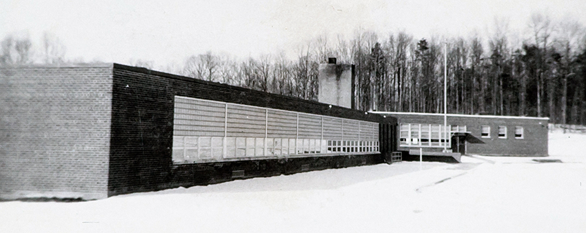 Black and white photograph of Cedar Lane Elementary School taken in 1958. The building is a one-story brick structure. There is snow on the ground.