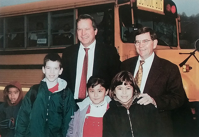 Photograph of Marshall Road Center's principal John Marston with Marshall Road Elementary's principal David Meadows. They are standing in front of a school bus with a group of four children.