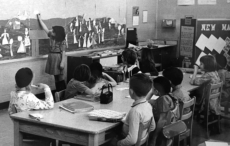 Black and white photograph of classroom 103, circa 1966. This was a primary-grade classroom, housing children in both first and second grades. A girl wearing a Brownie Scout uniform stands at a board along the wall which appears to have paper doll figures attached. A group of ten students, boys and girls, seated at a long wooden table look on. The children are seated on wooden chairs.