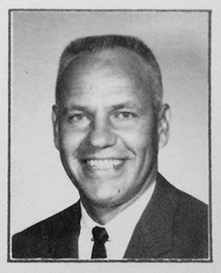 Black and white photograph of Principal Robert F. Jarecke. He is wearing a dark suit and tie and is smiling broadly.