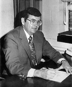Black and white photograph of Principal David L. Meadows from a Marshall Road yearbook. He is seated at the desk in his office, signing paperwork.