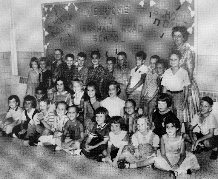 Black and white photograph of first grade teacher Mrs. Maude Foster with her students on the first day of school in 1961. There are thirty children pictured, boys and girls. They are photographed in a school hallway in front of a billboard that says Welcome to Marshall Road School.