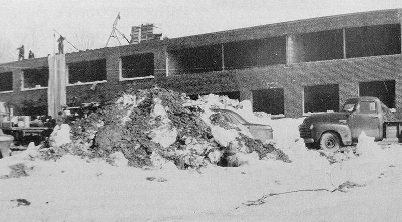 Black and white photograph of Marshall Road Elementary School during construction. The photograph was taken during the winter of 1961 because there is snow on the ground. The shell of the building is in place, but there are no windows. Workmen are visible on the roof.